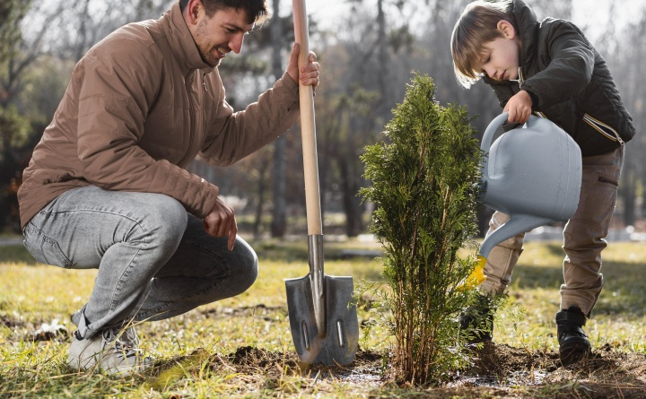 young-boy-planting-tree-outdoors-using-watering-can
